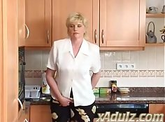 Blonde granny fucks herself with sex toys on the kitchen table